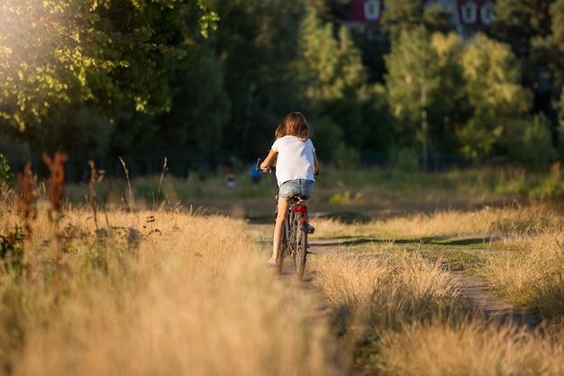 Getinte afbeelding van jonge vrouw die wegrijdt op de fiets op de weide