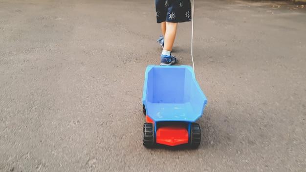 Getinte afbeelding van kleine peuterjongen die met een grote speelgoedvrachtwagen op de weg loopt