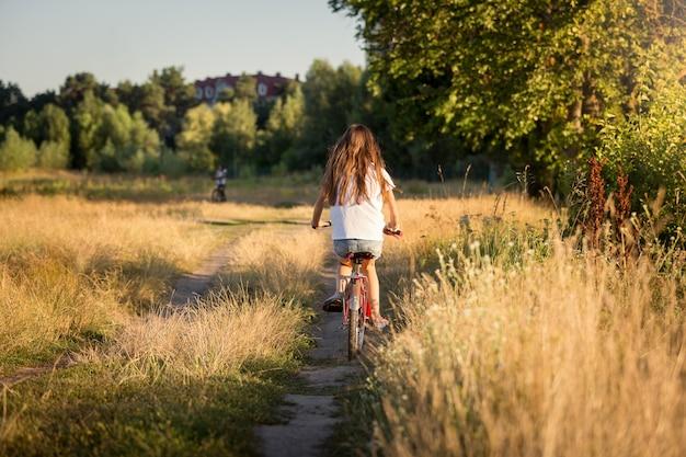 Getinte afbeelding van mooi meisje fiets op velden bij zonsondergang