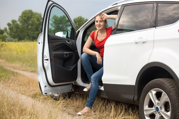 Getinte afbeelding van mooie jonge vrouw verdwaald tijdens het autorijden op het platteland