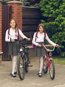 Getinte afbeelding van schattige lachende meisjes die met fietsen naar school gaan