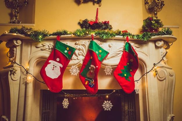 Getinte foto van drie rode kerstsokken die thuis aan de open haard hangen