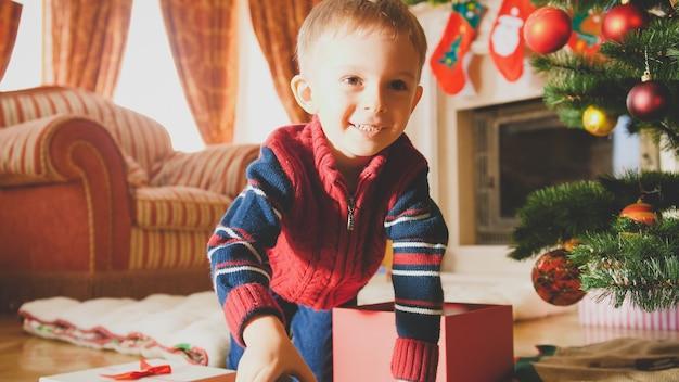 Getinte foto van een gelukkig lachend jongetje dat op de vloer kruipt onder een prachtig versierde kerstboom in de woonkamer
