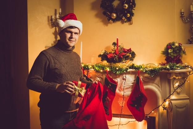 Getinte foto van een jonge glimlachende man die een geschenkdoos uit een rode kerstzak haalt