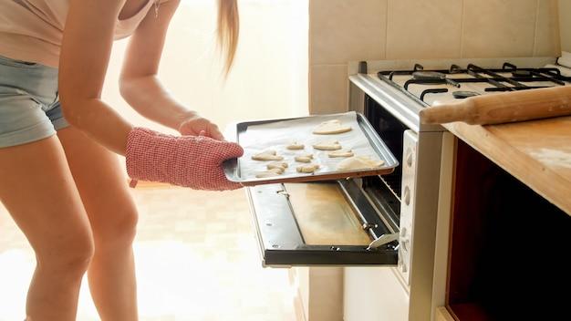 Getinte foto van een mooie glimlachende huisvrouw die een bakpan met rauwe koekjes in de hete oven in de keuken zet