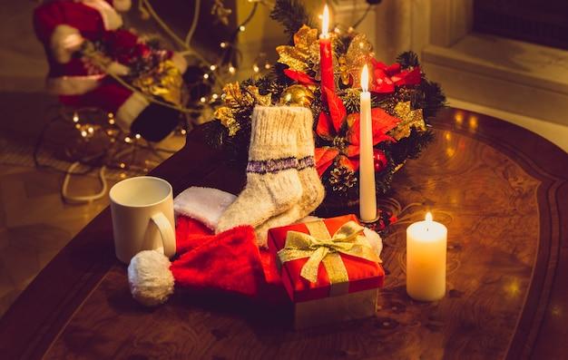 Getinte foto van kerstkaarsen, open geschenkdoos en wollen sokken op houten tafel bij open haard