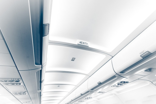 Getinte foto van lang plafond in vliegtuig met exit-teken