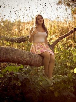 Getinte foto van schattige jonge vrouw zittend op een grote tak in het bos