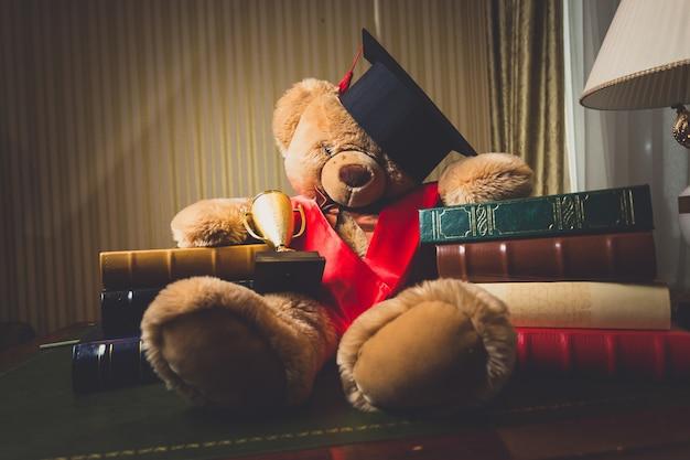 Getinte foto van teddybeer met afstudeerpet in bibliotheek