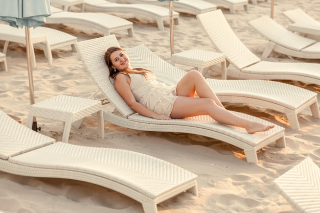 Getinte foto van vrouw in jurk liggend op zonnebank op leeg strand