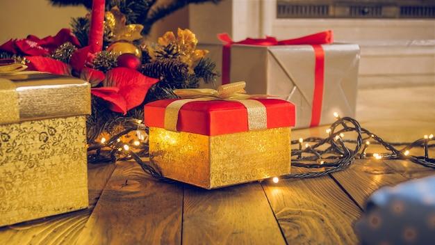 Getinte kerst achtergrond. gouden geschenkdoos, krans en gloeiende lichten op houten vloer in woonkamer