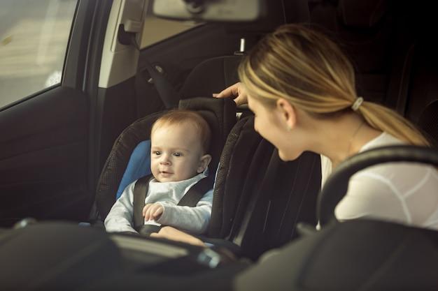 Getinte portret van moeder en babyjongen zittend in de auto op de voorstoelen