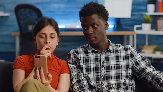 Getrouwd interraciaal stel dat smartphone thuis gebruikt