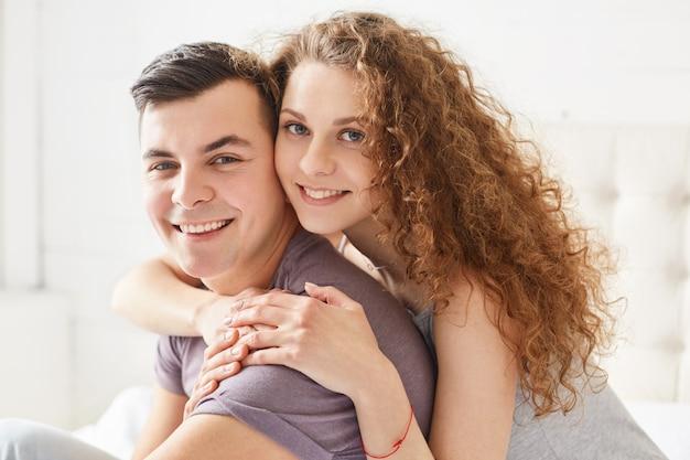 Getrouwde jonggehuwden met een positieve uitdrukking genieten thuis van een vrije dag. de glimlachende krullende vrouw omhelst met liefdeman