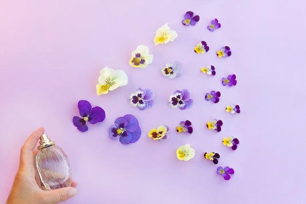 Geur, geur, parfumfles in de hand, fris bloemenaroma en bloemen, kleurrijke bloembladen