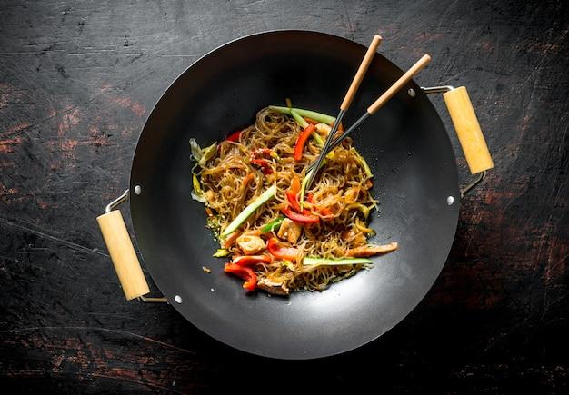 Geurige chinese cellofaannoedels in een koekenpanwok met salmonnd groenten op donkere rustieke tafel