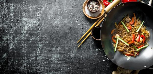 Geurige chinese cellofaannoedels met groenten op donkere houten lijst