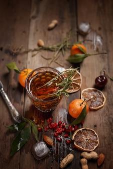 Geurige fruitthee met mandarijnen, gedroogde citroenen en rozemarijn op een houten tafel. landelijke stijl.