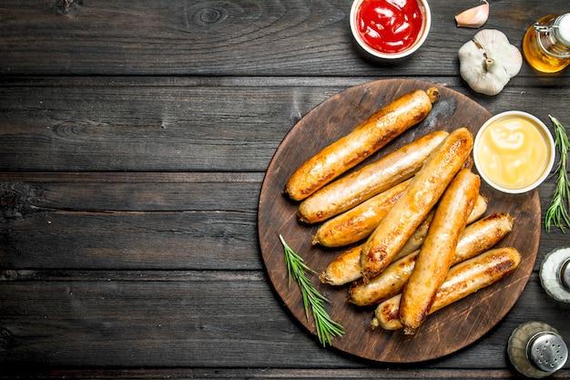 Geurige gegrilde worstjes met sauzen en kruiden op een houten tafel.