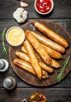 Geurige gegrilde worstjes met sauzen en kruiden op houten tafel.