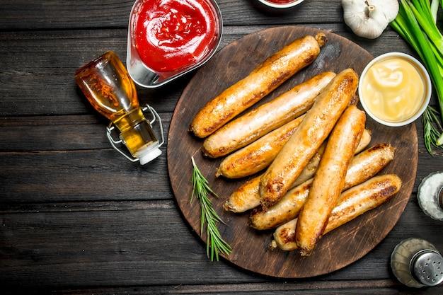 Geurige gegrilde worstjes met sauzen en kruiden op rustieke tafel.