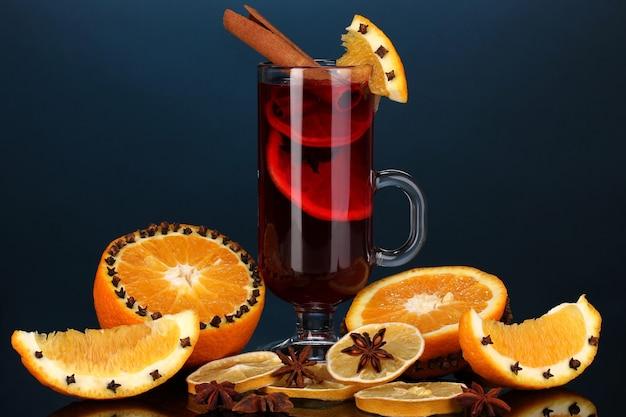 Geurige glühwein in glas met kruiden en sinaasappelen rond op blauwe achtergrond