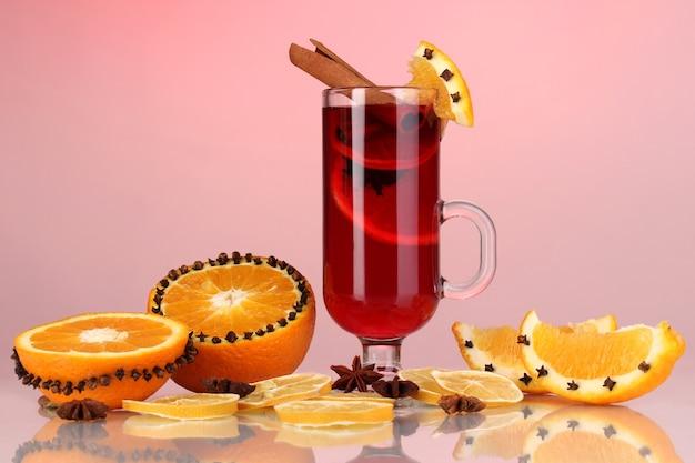 Geurige glühwein in glas met kruiden en sinaasappelen rond op rode achtergrond
