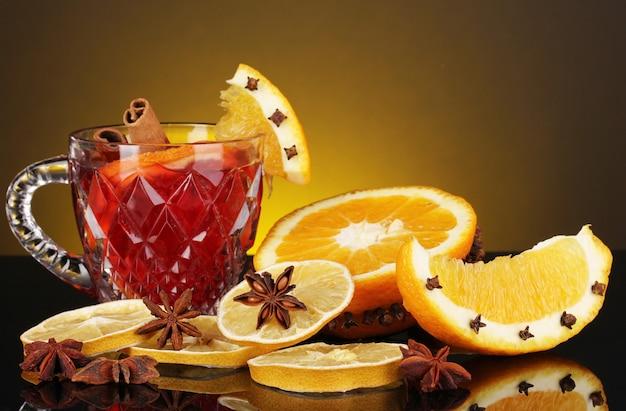 Geurige glühwein in glas met kruiden en sinaasappels rond op geel oppervlak