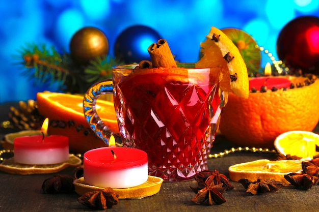 Geurige glühwein in glas met kruiden en sinaasappels rond op houten tafel op blauwe achtergrond