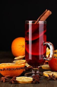 Geurige glühwein in glas met kruiden en sinaasappels rond op houten tafel