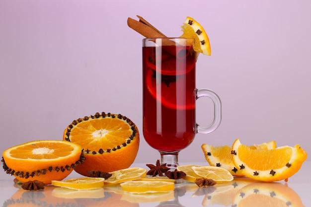 Geurige glühwein in glas met kruiden en sinaasappels rond op paarse achtergrond