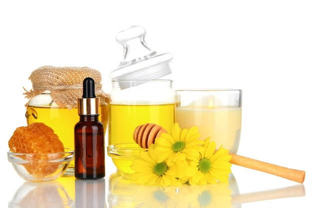 Geurige honing spa met oliën en honing op wit wordt geïsoleerd