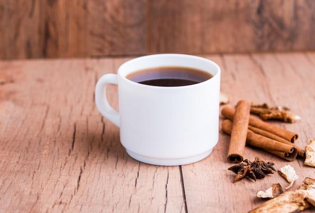Geurige natuurlijke custard koffie met kaneelstokjes, gedroogde paddestoelen, op een houten tafel