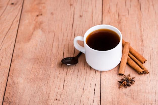 Geurige natuurlijke vla koffie met kaneelstokjes, gedroogde paddestoelen, op een houten achtergrond.