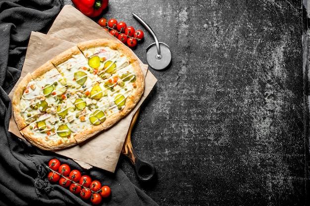 Geurige pizza met groenten en tomaten op een tak. op rustieke achtergrond