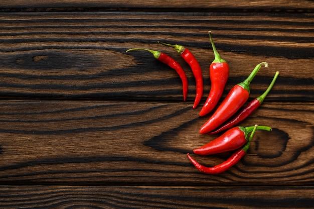 Geurige rode peper geïsoleerd op houten achtergrond, bovenaanzicht. biologische vegetarische voeding, kruideniersassortiment, natuurlijke ecoproducten, gezond levensstijlconcept