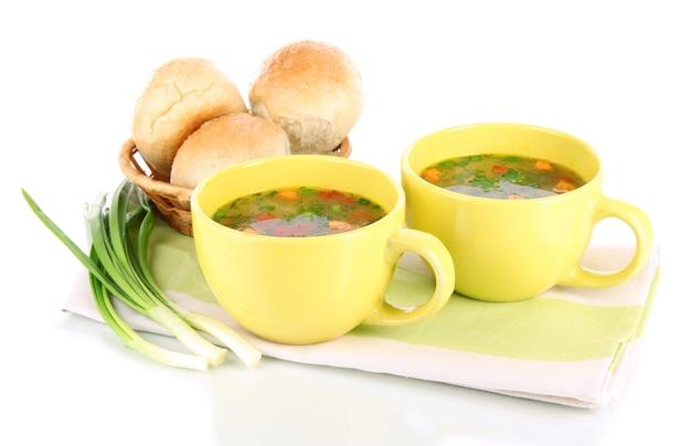 Geurige soep in kopjes geïsoleerd op wit