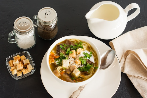 Geurige soep van witte verse champignons met peterselie en croutons. melkboer met room om de smaak te verbeteren.