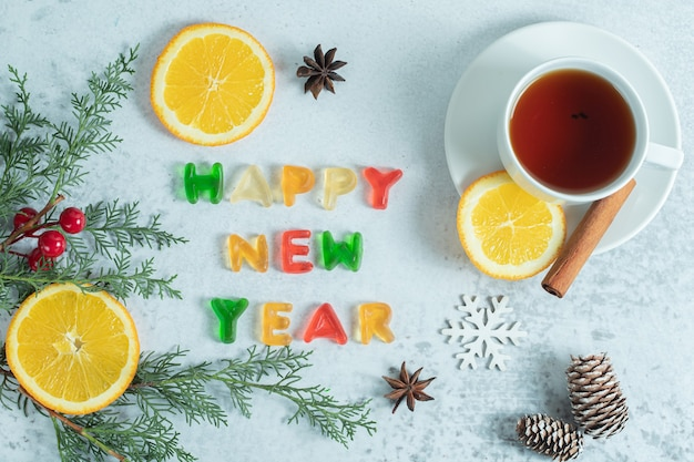 Geurige thee met gelei en stukjes sinaasappel op wit.