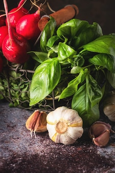 Geurige verse kruiden: basilicumbladeren, knoflook in een mand op tafel, ingrediënten voor het koken.