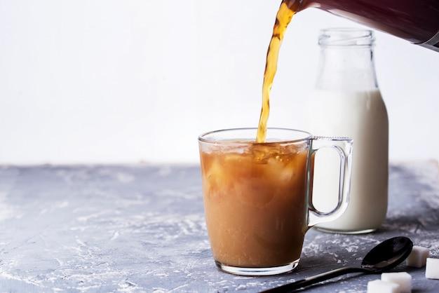 Geurige vla met melk, lepel, suiker, concrete achtergrond.