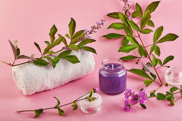 Geurkaars voor spa en thuis met lavendelgeur en groene bladeren op een roze ruimte.