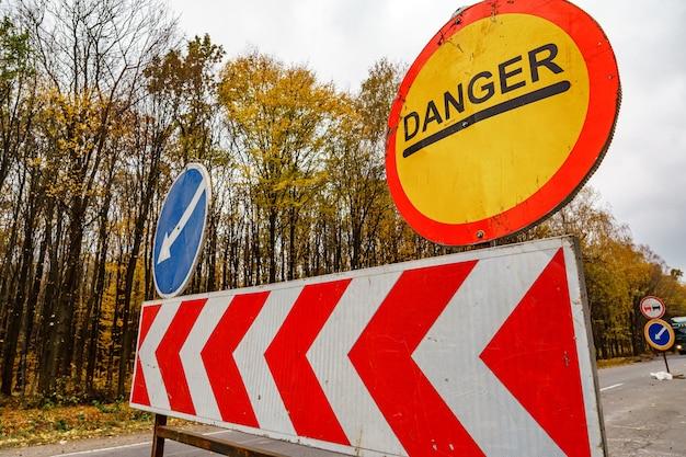 Gevaar verkeersbord op weg in rode cirkel op gele kleur. waarschuwing vooruit. aanwijzer op blauwe kleur in cirkel.