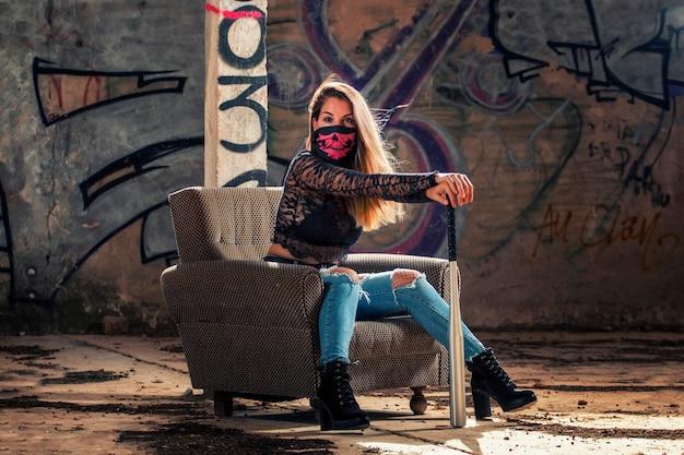 Gevaarlijk meisje met roze mondmasker op een verlaten fabriek die een oude bank gebruikt.
