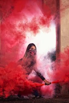 Gevaarlijk meisje met roze mondmasker op een verlaten fabriek met een rookgranaat.