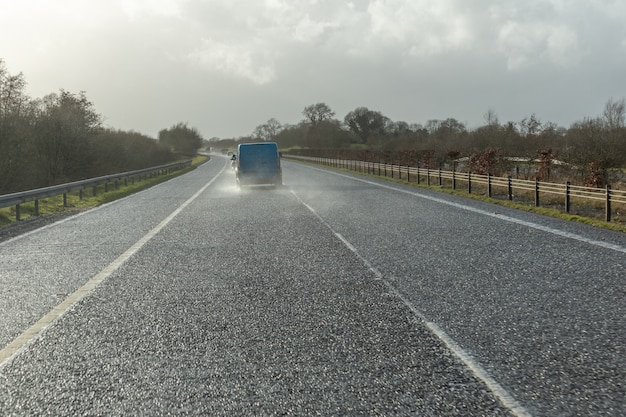 Gevaarlijk voertuig dat op de zware regenachtige en gladde weg rijdt. samenvatting wazig slecht weer auto op de snelweg.