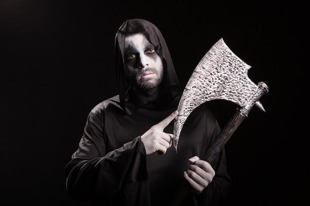 Gevaarlijke enge man verkleed als magere hein met een bijl op zwarte achtergrond.