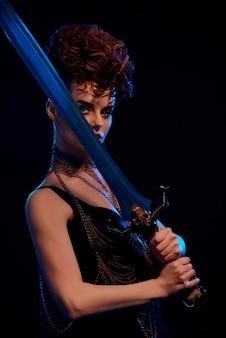 Gevaarlijke krijgersvrouw die groot stalen zwaard houdt.