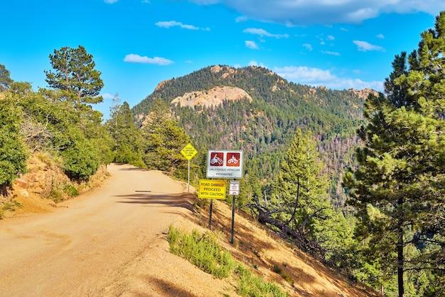 Gevaarlijke onverharde weg in bergen met waarschuwingsborden ga voorzichtig te werk