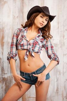 Gevaarlijke schoonheid. mooie jonge cowgirl gebaren en kijken naar de camera terwijl je tegen de houten achtergrond staat